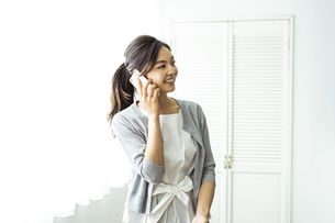 スマートフォンで話す30代日本人女性の写真素材 [FYI04591796]