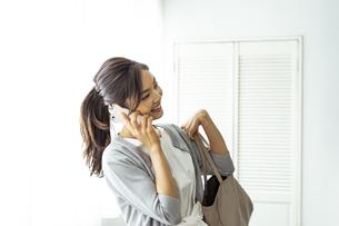 スマートフォンで話す30代日本人女性の写真素材 [FYI04591800]