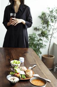 食卓の上のブレックファーストと飲み物を持つ女性の写真素材 [FYI04591808]