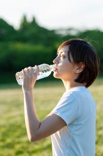 公園で水分補給をする女性の写真素材 [FYI04591983]
