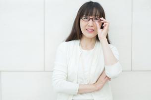 メガネを持ち上げる女性の写真素材 [FYI04592104]