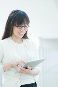 廊下でタブレットを操作する女性の写真素材 [FYI04592118]