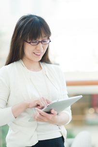 オフィスでタブレットを操作する女性の写真素材 [FYI04592119]