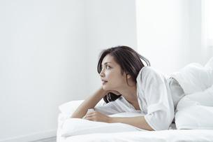 ベッドで横になる30代日本人女性の写真素材 [FYI04592256]
