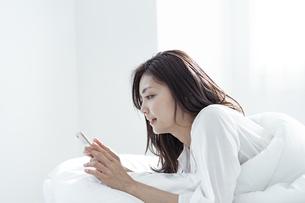 ベッドで横になりスマートフォンを見る30代日本人女性の写真素材 [FYI04592260]