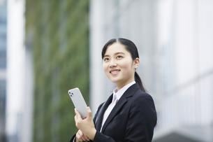 スマートフォンを持つスーツを着た笑顔の若い女性の写真素材 [FYI04592815]