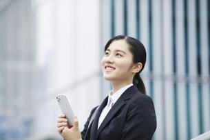 スマートフォンを持つスーツを着た笑顔の若い女性の写真素材 [FYI04592818]