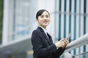 スマートフォンを持つスーツを着た笑顔の若い女性の写真素材 [FYI04592838]