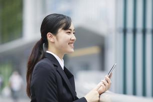 スマートフォンを持つスーツを着た笑顔の若い女性の写真素材 [FYI04592842]
