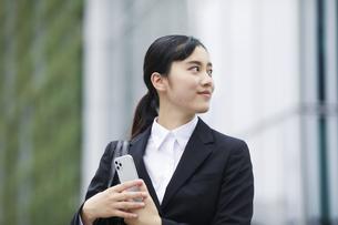 スマートフォンを持つスーツを着た笑顔の若い女性の写真素材 [FYI04592847]