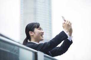 スマートフォンを持つスーツを着た笑顔の若い女性の写真素材 [FYI04592849]