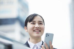 スマートフォンを持つスーツを着た笑顔の若い女性の写真素材 [FYI04592853]