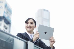 タブレットPCを持つスーツを着た笑顔の若い女性の写真素材 [FYI04592864]