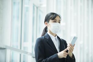 マスクをしながらスマートフォンを持つスーツを着た若い女性の写真素材 [FYI04592866]