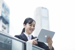 タブレットPCを持つスーツを着た笑顔の若い女性の写真素材 [FYI04592870]