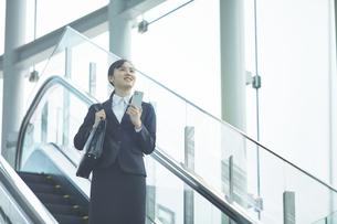 スマートフォンを持つスーツを着た笑顔の若い女性の写真素材 [FYI04592877]