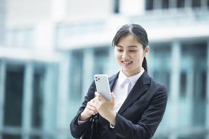 スーツを着てスマートフォンを持つ若い女性の写真素材 [FYI04592886]