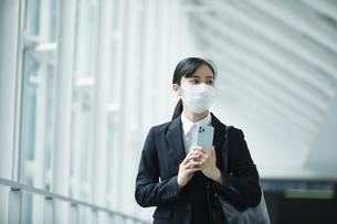 スーツを着てマスクをする若い女性の写真素材 [FYI04592887]