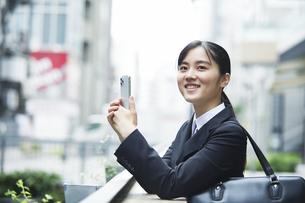 スーツを着てスマートフォンを持つ若い女性の写真素材 [FYI04592896]