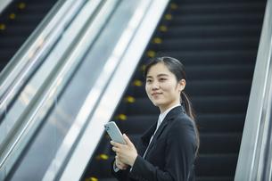 スーツを着てスマートフォンを持つ若い女性の写真素材 [FYI04592897]