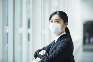 スーツを着てマスクをする若い女性の写真素材 [FYI04592900]