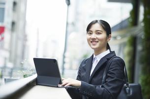 スーツを着てタブレット端末を操作する若い女性の写真素材 [FYI04592905]