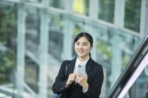 スーツを着てスマートフォンを持つ若い女性の写真素材 [FYI04592911]