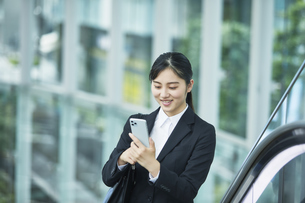 スーツを着てスマートフォンを持つ若い女性の写真素材 [FYI04592913]