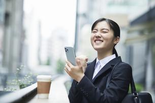 スーツを着てスマートフォンを持つ若い女性の写真素材 [FYI04592920]
