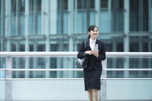 スーツを着てスマートフォンを持つ若い女性の写真素材 [FYI04592925]
