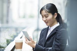 スーツを着てスマートフォンを持つ若い女性の写真素材 [FYI04592933]