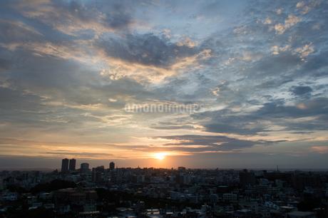 夕日でオレンジ色になった雲とシルエットの街並みの写真素材 [FYI04593430]