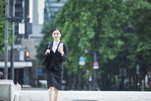 スマートフォンを持つスーツを着た若い女性の写真素材 [FYI04593455]