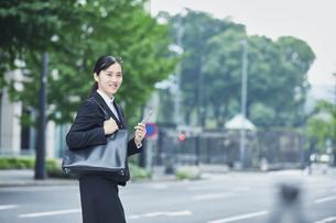 スマートフォンを持つスーツを着た笑顔の若い女性の写真素材 [FYI04593471]
