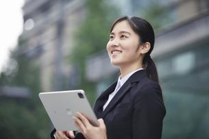 タブレットPCを持つスーツを着た笑顔の若い女性の写真素材 [FYI04593496]