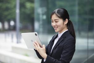 タブレットPCを持つスーツを着た笑顔の若い女性の写真素材 [FYI04593498]