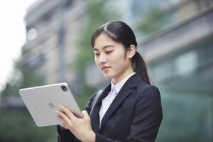 タブレットPCを持つスーツを着た笑顔の若い女性の写真素材 [FYI04593501]