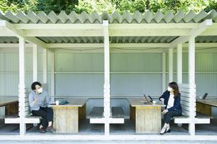 テラス席で仕事の合間に会話する男女の写真素材 [FYI04594126]