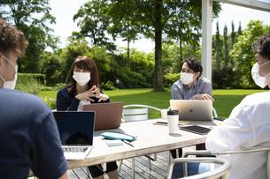 テラス席でマスクを着けてミーティングする男女の写真素材 [FYI04594167]
