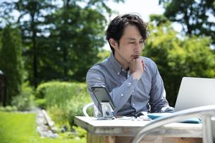 テラス席で仕事をするミドルの男性の写真素材 [FYI04594383]