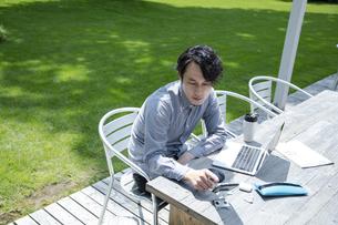テラス席で仕事をするミドルの男性の写真素材 [FYI04594418]