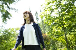 ガーデンを歩くミドルの女性の写真素材 [FYI04594469]