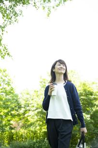 ガーデンを歩くミドルの女性の写真素材 [FYI04594482]