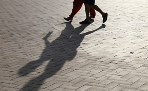 石畳の歩道の人影の写真素材 [FYI04595014]