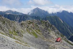 夏の槍ヶ岳の登山道から見下ろす山小屋と遠くに見える常念岳の写真素材 [FYI04595153]