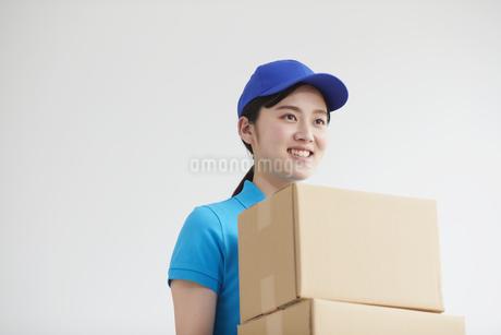 作業服を着て笑顔で荷物を運ぶ若い女性の写真素材 [FYI04595977]
