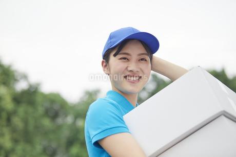 作業服を着て笑顔で荷物を運ぶ若い女性の写真素材 [FYI04595978]