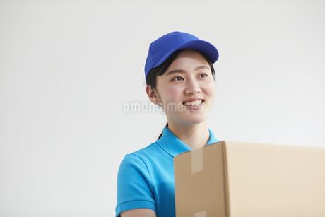 作業服を着て笑顔で荷物を運ぶ若い女性の写真素材 [FYI04595979]
