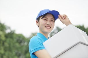 作業服を着て笑顔で荷物を運ぶ若い女性の写真素材 [FYI04595980]