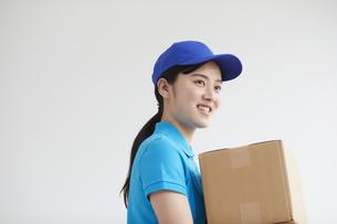 作業服を着て笑顔で荷物を運ぶ若い女性の写真素材 [FYI04595981]